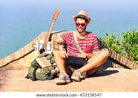 Handsome traveler man using pc sitting down by blue ocean background - Happy guy relaxing with laptop at sea view point - Concept of freedom and summer trip around the world backpacker style -  - stock photo
