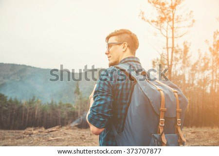 Handsome traveler young man with backpack walking in the forest at sunny day - stock photo