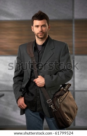 Handsome trendy office worker standing in lobby holding laptop bag looking at camera confidently. - stock photo