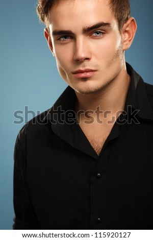 Handsome trendy young man in black shirt, portrait of sexy fashion boy looking right over dark blue background - stock photo