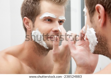 Handsome unshaven man looking into the mirror in bathroom - stock photo