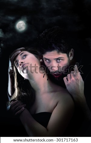 handsome vampire biting girl isolated in dark background - stock photo
