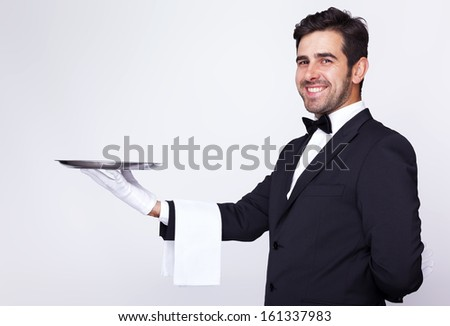 Handsome waiter holding an empty silver tray over gray background - stock photo