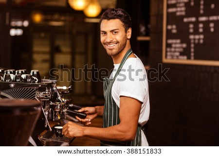 Handsome waiter serving coffee cup at the coffee shop - stock photo