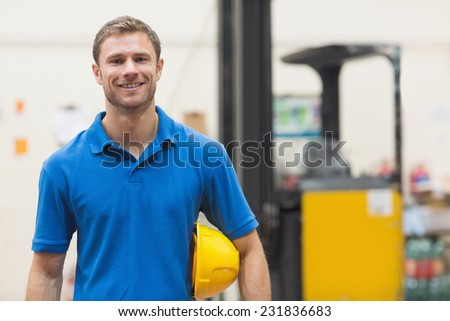 Handsome warehouse worker smiling at camera in a large warehouse - stock photo