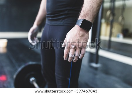 Handsome weightlifter preparing for training. Depth of field, selective focus - stock photo