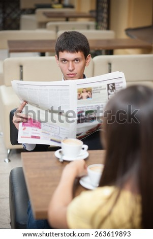 Handsome with newspaper. Young man with newspaper posing for camera across table with cup of coffee - stock photo