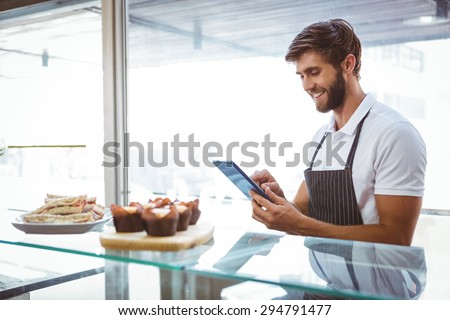 Handsome worker posing on the counter with a tablet at the bakery - stock photo