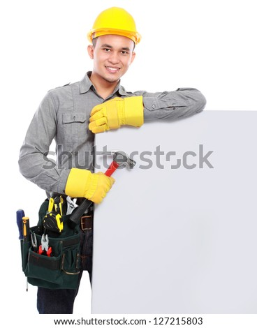 handsome worker with tool belt hold a banner - stock photo