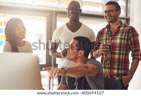 Handsome young adult showing something on his computer to a group of three male and female casually dressed friends holding drinks - stock photo