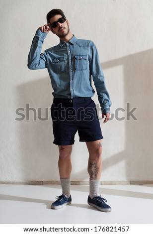 handsome young adult wearing casul clothes and sunglasses posing for camera - stock photo