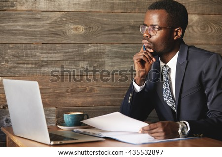 Handsome young African man wearing formal suit sitting at a coffee shop with pensive look, thinking of business plans, holding a pen, leaning his elbow on the table, signing papers, working on laptop - stock photo