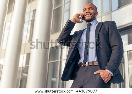 Handsome young Afro American businessman in classic suit talking on the mobile phone and smiling, standing outdoors near the office building - stock photo