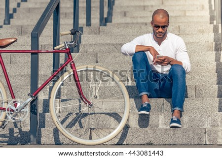 Handsome young Afro American man in casual wear and sun glasses is using smartphone while sitting on stairs outdoors - stock photo