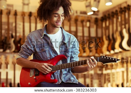 Handsome young Afro-American man in jeans jacket smiling while playing an electric guitar in a musical shop - stock photo