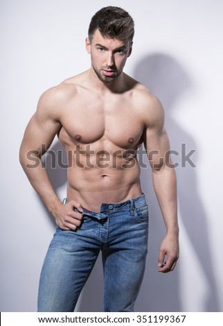 handsome young and fit bodybuilder posing shirtless on grey background - stock photo