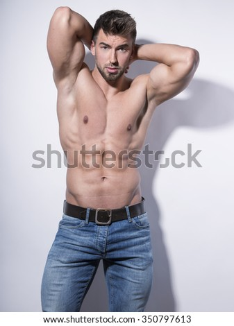 handsome young and fit bodybuilder with toned body on grey background - stock photo