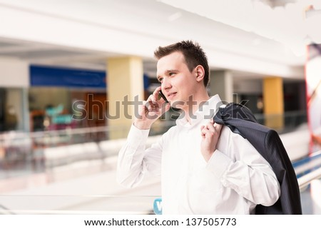 Handsome young and successful businessman talking on his mobile phone in a business center - stock photo