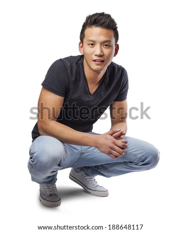 handsome young asian man sitting on the floor on white - stock photo