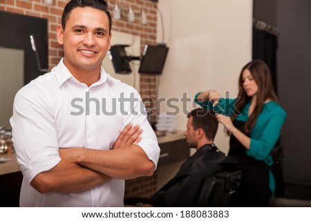 Handsome young barber shop owner smiling and managing his business - stock photo