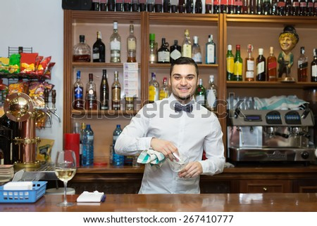 Handsome young bartender working at counter of night club - stock photo