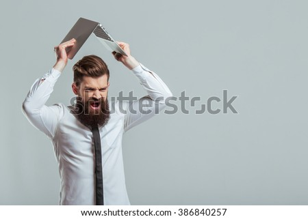 Handsome young bearded businessman in classic white shirt is holding a laptop overhead and screaming, on a gray background - stock photo