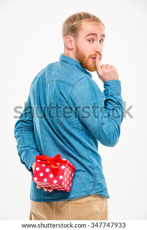 Handsome young bearded man hiding gift behind back and gesturing silence over white background - stock photo