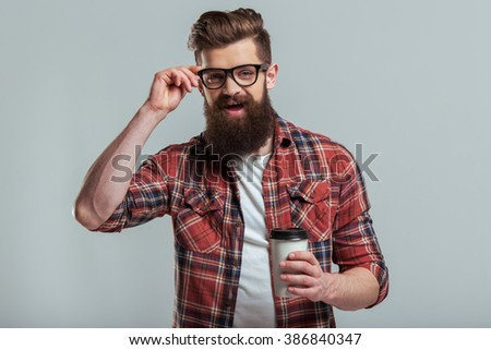 Handsome young bearded man in casual clothes and eyeglasses is smiling and holding a cup, on a gray background - stock photo