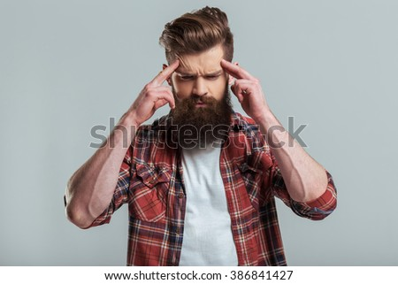 Handsome young bearded man in casual clothes is looking a camera and keeping fingers on forehead, on a gray background - stock photo