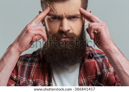 Handsome young bearded man in casual clothes is looking a camera and keeping fingers on forehead, on a gray background, close-up - stock photo
