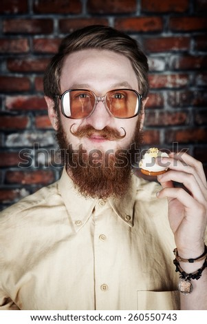 Handsome young bearded man in sunglasses with cake looking at camera and smiling - stock photo