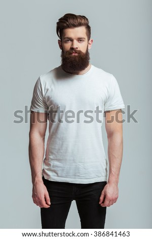Handsome young bearded man is looking at camera while standing against gray background - stock photo