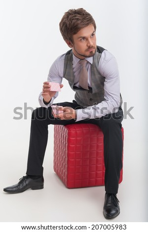 Handsome young bearded man wearing nice waistcoat and tie sitting on the red pouffe and shuffling cards. Isolated on white background - stock photo