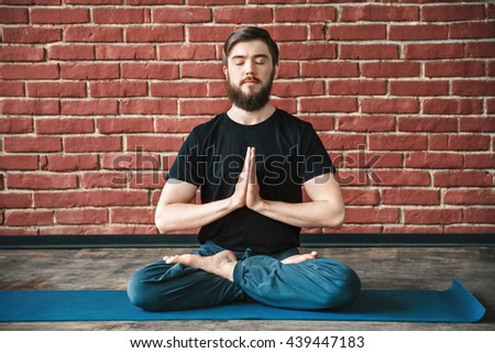 Handsome young bearded man with closed wearing black T-shirt sitting on blue matt doing yoga position at wall background, namaste mudra, copy space. - stock photo