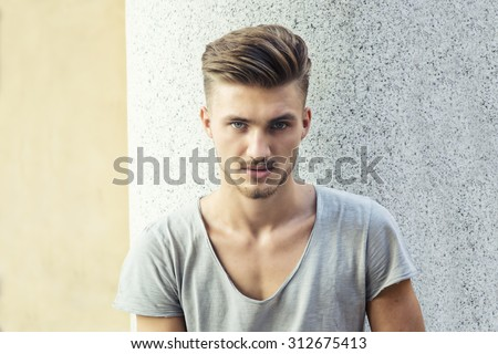 Handsome young blond man standing outdoors against marble wall, looking at camera - stock photo