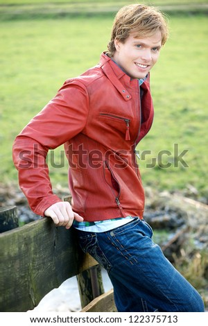 Handsome young blonde male relaxing outdoor. Fashion model is wearing red leather jacket and blue jeans with a friendly facial expression. - stock photo