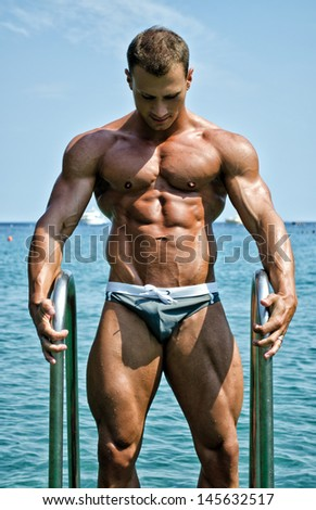 Handsome young bodybuilder getting out of sea or ocean water looking at his muscular torso, pecs, arms and abs - stock photo