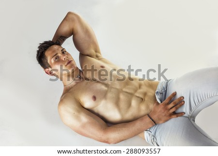 Handsome young bodybuilder laying down on the floor, showing ripped abs, muscular pecs, arms - stock photo