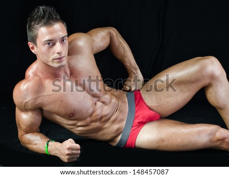 Handsome young bodybuilder laying down on the floor, showing ripped abs, muscular  pecs, arms and legs - stock photo