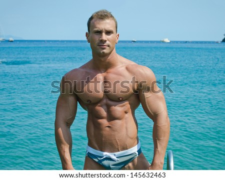 Handsome young bodybuilder standing with sea or ocean behind showing muscular torso, pecs, arms and abs - stock photo