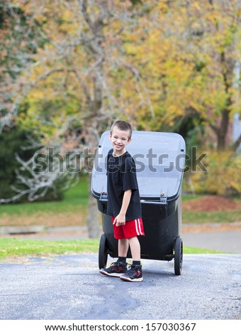 Handsome young boy bringing trash can up the driveway - stock photo