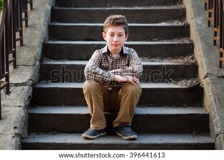 Handsome young boy portrait. Stylish smiling kid boy sitting on the stairs on the street and looking at camera. Teenage boy, child outdoors in summer or spring. - stock photo