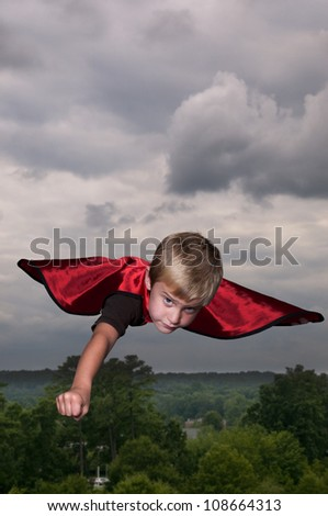 Handsome young boy super hero flying through the sky - stock photo