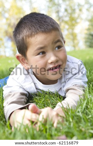 Handsome young boy with bright smile missing one front tooth laying in the grass - stock photo