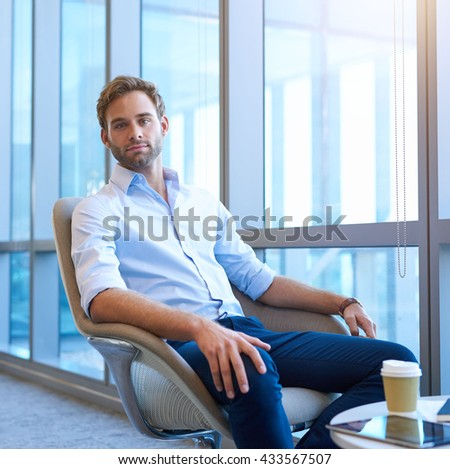 Handsome young business entrepreneur, sitting in a bright modern space alongside large windows, looking at the camera with a serious yet optimistic expression - stock photo