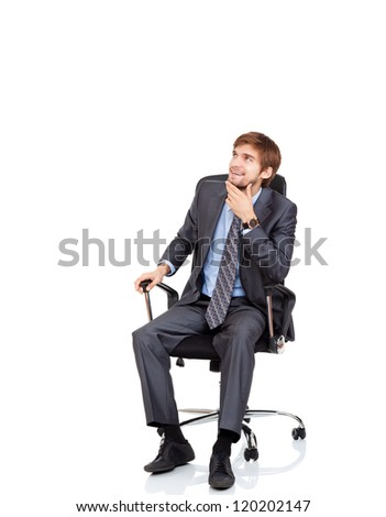 Handsome young business man happy smile look up to empty copy space sitting in chair, businessman think, idea, hold hand finger on chin wear elegant suit and tie isolated over white background - stock photo