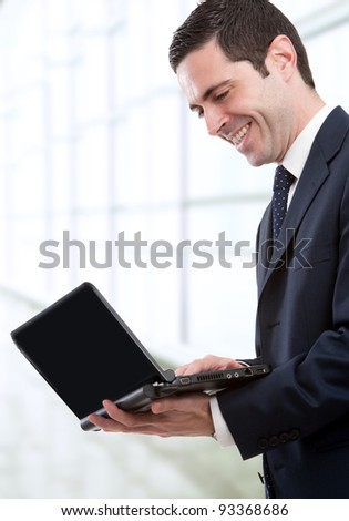 Handsome young business man in blue suit standing with laptop in office. - stock photo