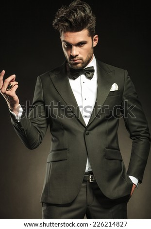 Handsome young business man looking at the camera while snapping his fingers, holding one hand in pocket. - stock photo