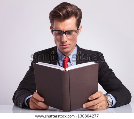 handsome young business man reading a book at his desk, on gray background - stock photo