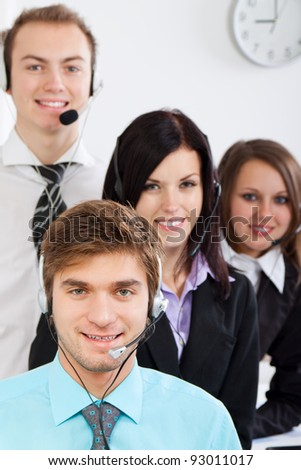 handsome young businessman and colleagues in a call center office, Attractive Smiling  businesspeople in support phone, operators with headset at workplace, agent friendly looking at camera - stock photo
